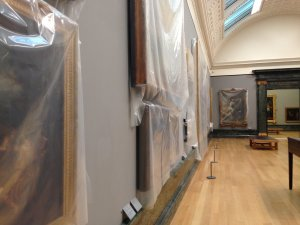 Tate Britain gallery with plastic-wrapped paintings.